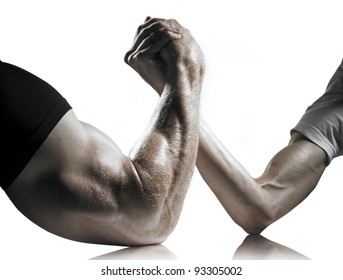 A heavily muscled man arm wrestling a puny weak man