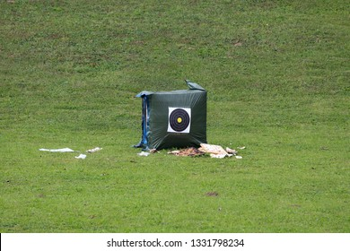 Heavily used archery practice target for bow and arrows mounted on large nylon covered hay bale surrounded with used targets and freshly cut grass on warm sunny day