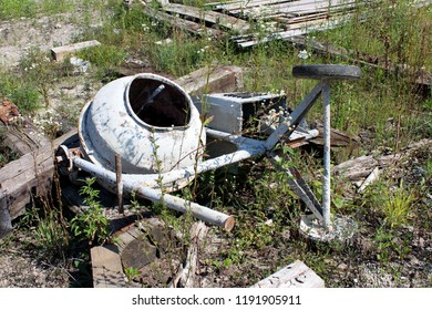Heavily used broken and partially rusted electric concrete mixer with dried concrete all over metal discarded on construction site surrounded with broken wooden beams and tall uncut grass and other sm