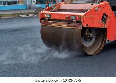 Heavy asphalt roller that stack and press hot asphalt. Road repair machine. Repairing in modern city with vibration roller compactor