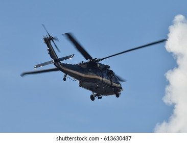 heavy black helicopter in flight rear view