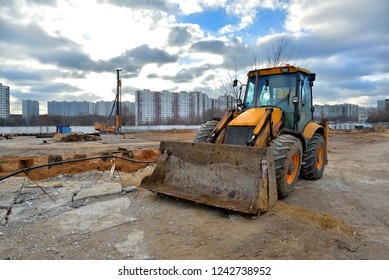 Heavy bulldozer and pile driving machine on a construction site.