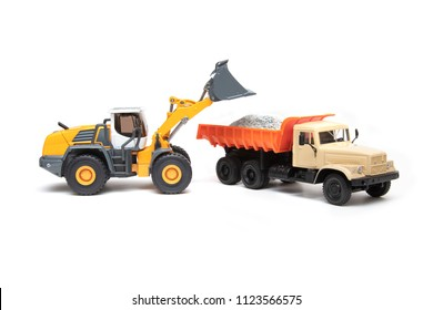 The heavy bulldozer of yellow color on a white background is loading of heavy dump-body truck