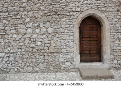 Heavy closed door on a stone wall of a medieval fortress, made of riveted wood