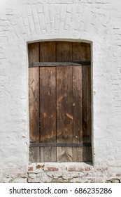 Heavy closed door on a stone wall of a medieval fortress