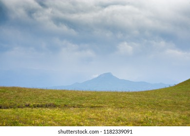 Heavy clouds over mountain peak. Summer day. Horizontal shot