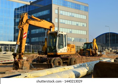 Heavy construction equipment and earthmoving excavators working on a construction site in the city. Laying or replacement of underground storm sewer pipes.