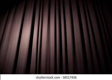 Heavy dark blue curtain with background texture and copy space.  Angled view.  Spotlight creating natural vignette.