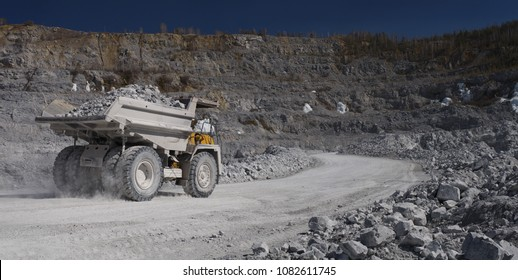 Heavy dump-body truck loaded with limestone ore moves along the road in a quarry, back view, panorama. Mining industry. Heavy equipment.