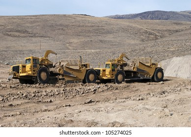 Heavy duty earth scrapers operating in tandem