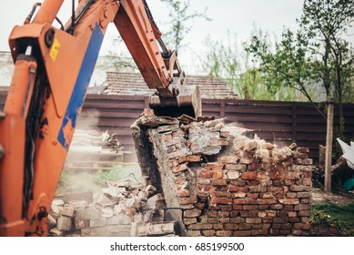 Heavy duty industrial backhoe excavator and bulldozer demolishing old house and ruins