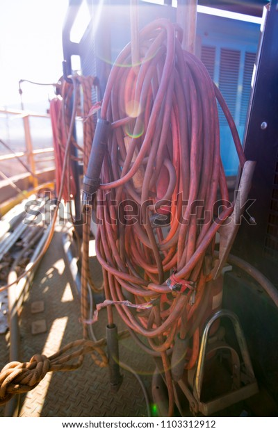Heavy duty industrial red welding equipment hang on aside generator at construction mining site Perth, Australia