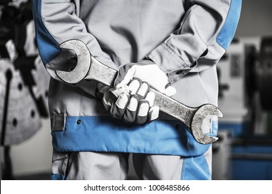Heavy Duty Machinery Mechanic on a Duty with Huge Metal Wrench in Hands.