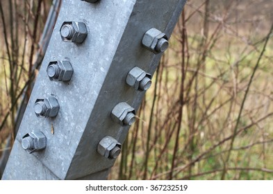 Heavy duty metal nuts and bolt holding steel structure together in a natural remote setting.