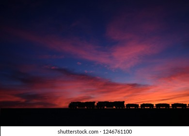heavy duty ore Train in the Sahara desert during dramatic sunset