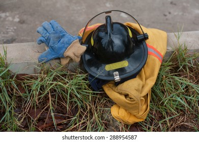 Heavy Duty Protective Fire Fighting Cloth, Gloves, Helmet, Jacket, Pants, on Green Grass Background
