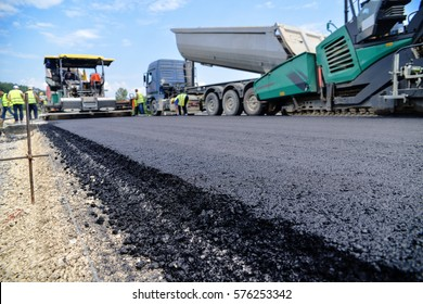 Heavy duty road building. Hot Asphalt being laid and measured for a quality check as a part of a on site control test.