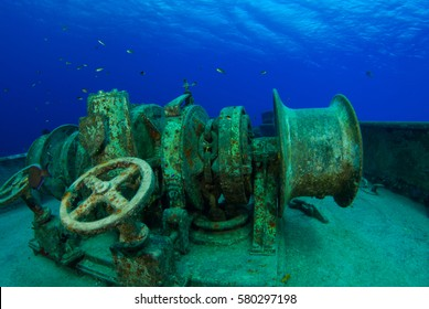 Heavy duty winches sit on the bow deck of a sunken ship. This machinery that is now becoming old and rusty is a feature of interest for scuba divers that enjoy wreck diving on the submerged Kittiwake