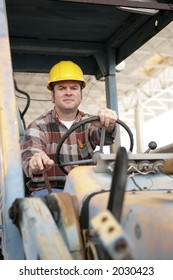 A heavy equipment operator driving a backhoe.