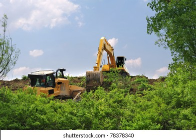 Heavy equipment strips all the vegetation off the side of a hill