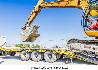 Heavy excavator it climbs on low platform trailer over back ramp, carrying two buckets inserted into one another.