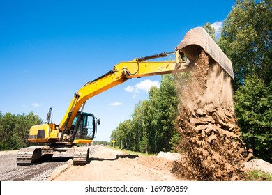 Heavy excavator unloading sand during road construction works