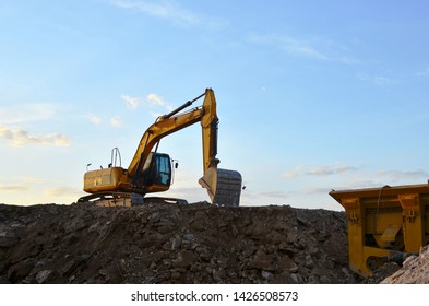Heavy excavator working at construction site. Crushing and processing of rocks in the mining quarry. Production of building stone and crushed stone