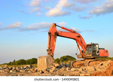 A heavy excavator in a working at granite quarry unloads old concrete stones for crushing and recycling to gravel or cement. Special heavy construction equipment for road construction.