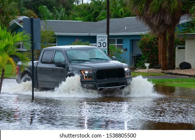 Heavy flooding and storm surge in residential neighborhood with a big truck driving through deep splashing water in the flooded street in front of houses.