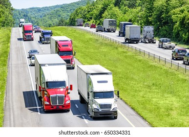 A heavy flow of 18-wheelers peppered with cars and SUVs roll down a Tennessee interstate highway.  Heat rising from the pavement gives a shimmering effect to vehicles and background in the distance.
