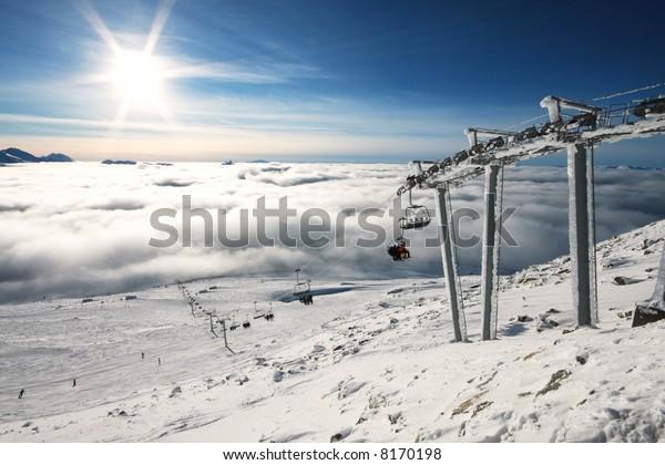 2010年の冬季オリンピック開催地、バリカ合衆国のウイスラーでは、高山地が輝かしい日差しを浴び、深い霧が下の山を覆っている。