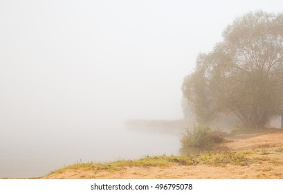 Heavy fog over the lake. Yellow sand on the shore.