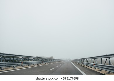 Heavy fog reduces visibility. Travelling down a road with barriers on both sides, in Tuscany, Italy, looking forward through a car windscreen.
