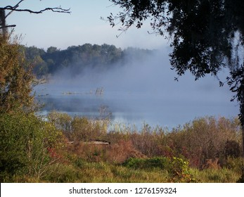 Heavy fog rises from a small lake early in the morning