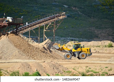 Heavy front-end loader or all-wheel bulldozer for mechanization of loading, digging and excavation operations in open quarry. Crusher plant with belt conveyor, crushing process, grinding stone