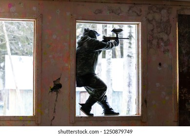 Heavy grain grunge style portrait of paintball player standing on window sill