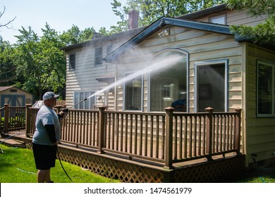 Heavy husband power washing large windows on the back of a house over a brown wooden deck with a pressure washer