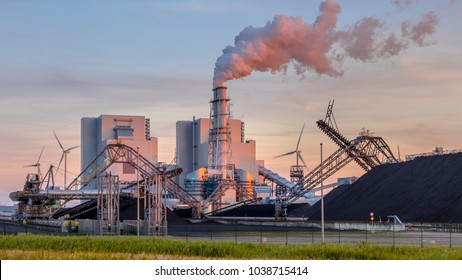 Heavy industrial coal powered electricity plant with pipes and smoke in orange light of setting sun