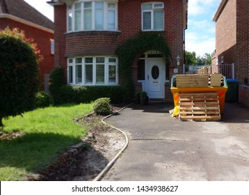 Heavy industrial rubbish skip on driveway. Selective focus on full metal bin in front of brick house with blurry surrounding area as space to add text for background use. Renovate, moving, concept.