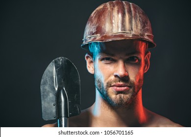 Heavy industry and labour concept - muscle sexy builder, repairman in protective helmet with spade. Unshaven man with confident face expression holds shovel in hand. Army man holds sapper shovel.