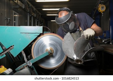 Heavy industry manual worker with big grinder and boat propeller