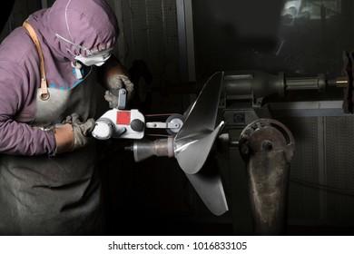 Heavy industry worker whit grinder boat propeller