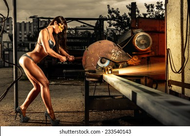 Heavy industry. Young sporty woman in swimsuit working with heavy tools