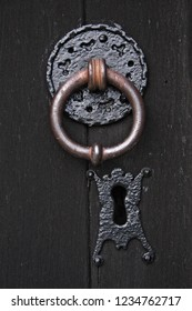 Heavy iron knocker, a little aged and rusted, set upon a patterned plate into a sturdy old wooden door. Keyhole below