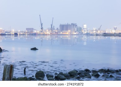 Heavy lit Industrial harbor reflected in the bland sea/Harbor background/Photography Sweden