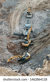 Heavy machinery excavators working on quarry and loading stone and granite into dump trucks. Bird eye perspective photo.