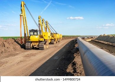 Heavy Machinery and Gas Pipeline Construction Site. Pipes are Laid on Top of Supportive Sandbags Beside Trench and Welded Together. Gas Pipeline Installation and Construction.
