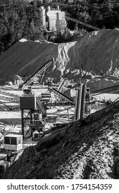 Heavy Machinery and other equipment at a crushed stone quarry by a cement plant. Natural resources in black and white series.
