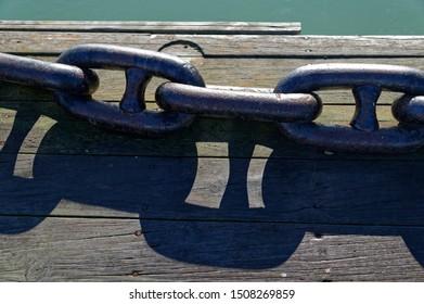 A heavy metal anchor chain lies on a wooden wharf