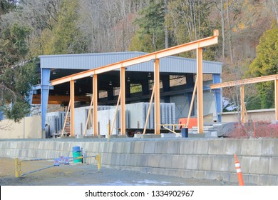 Heavy metal beams are used to construct an open, airy factory building.